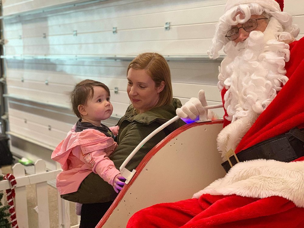 Lottie and Mummy stood looking up at Santa on his sleigh