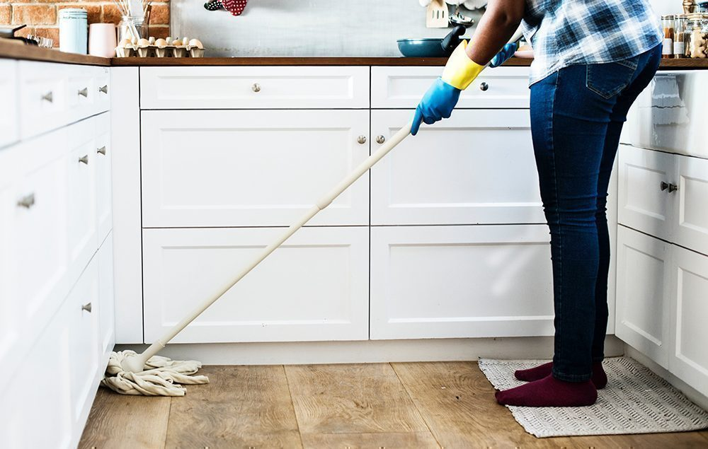 Lady mopping the kitchen floor in front of white units