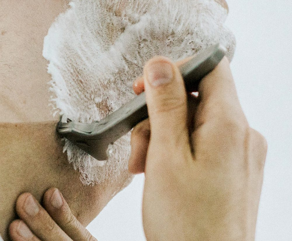 Man shaving his face with a razor