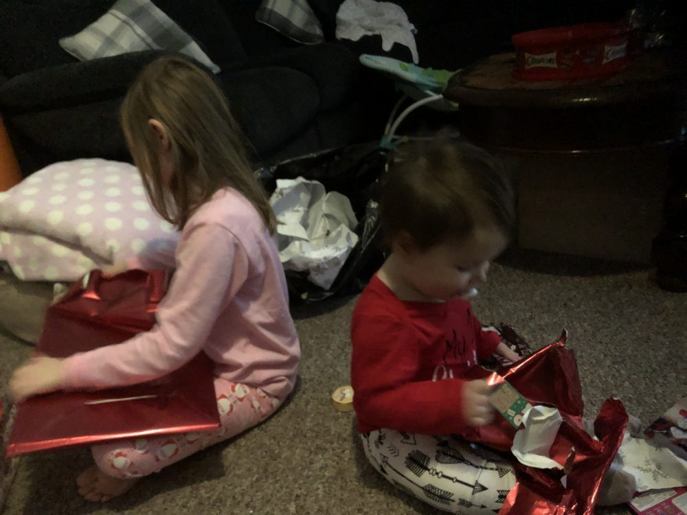 Lottie and Mia sat back to back opening presents wrapped in red paper
