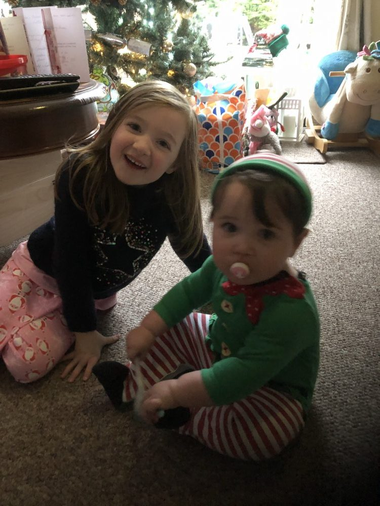Lottie dressed as an elf and Lottie sat in front of the christmas tree