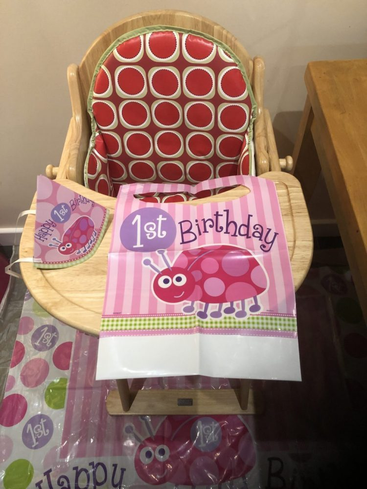 Wooden High Chair with red patterned insert. Decorated with 1st birthday banner, hat and bib with a pink ladybird on it