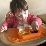 Lottie eating her lunch from an orange Mini EasyMat. Suctioned to a wooden high chair tray