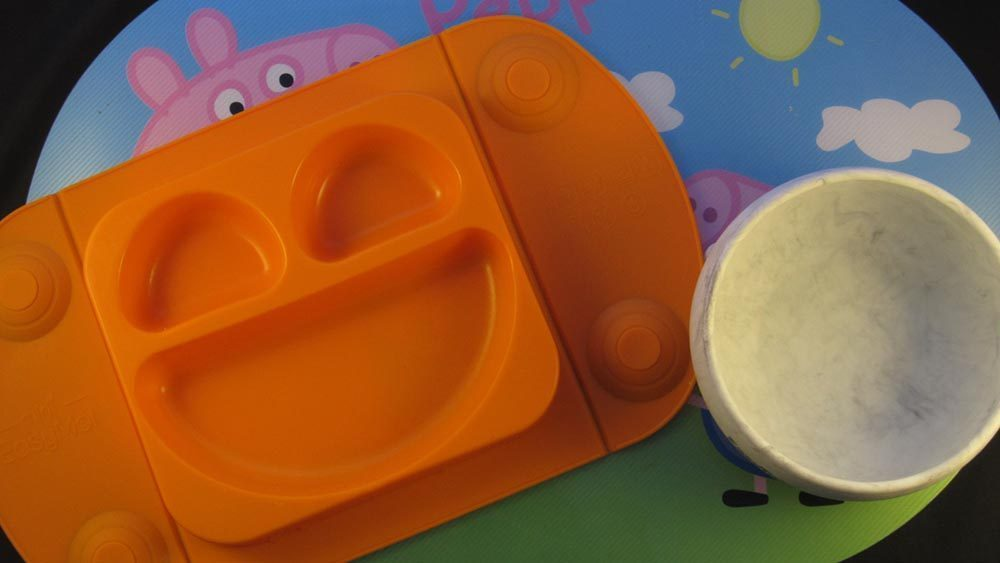 Orange mat and grey bowl on top of peppa pig mat