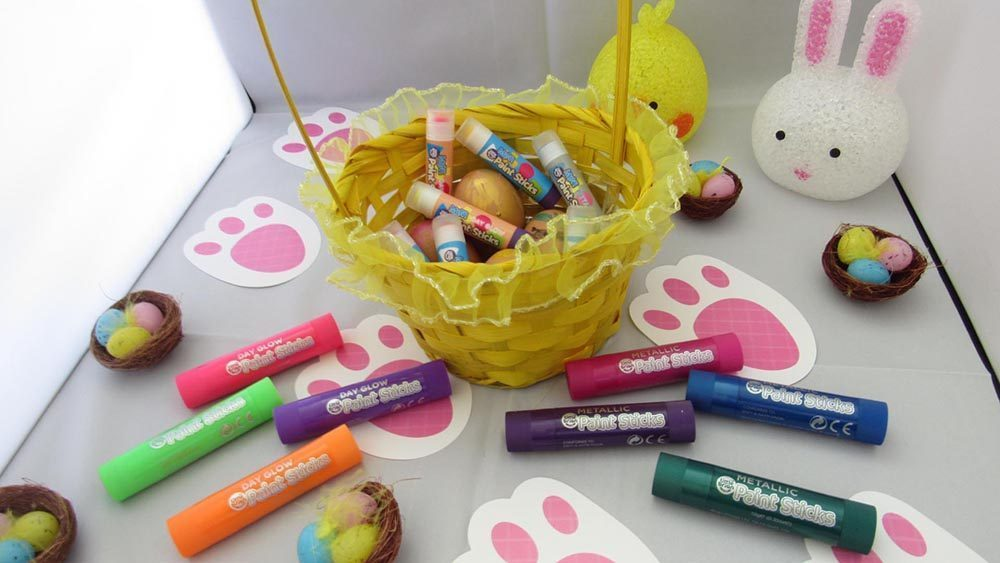 yellow basket of paint sticks and eggs surrounded by more paint sticks, easter nests and bunny footprints