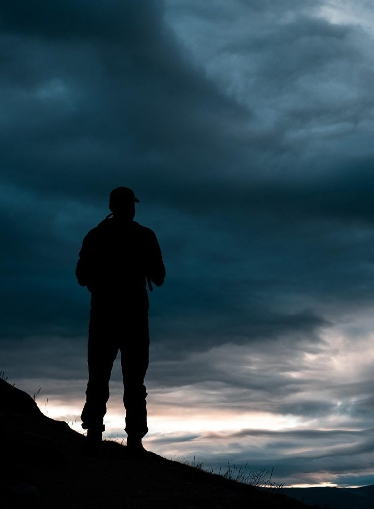 Man standing on his own looking out over a sunset. Support Group positives