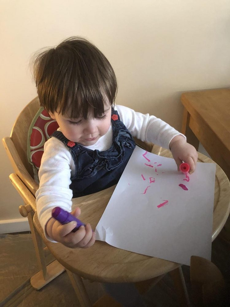 Lottie using paint sticks to paint pink and purple splurges on paper