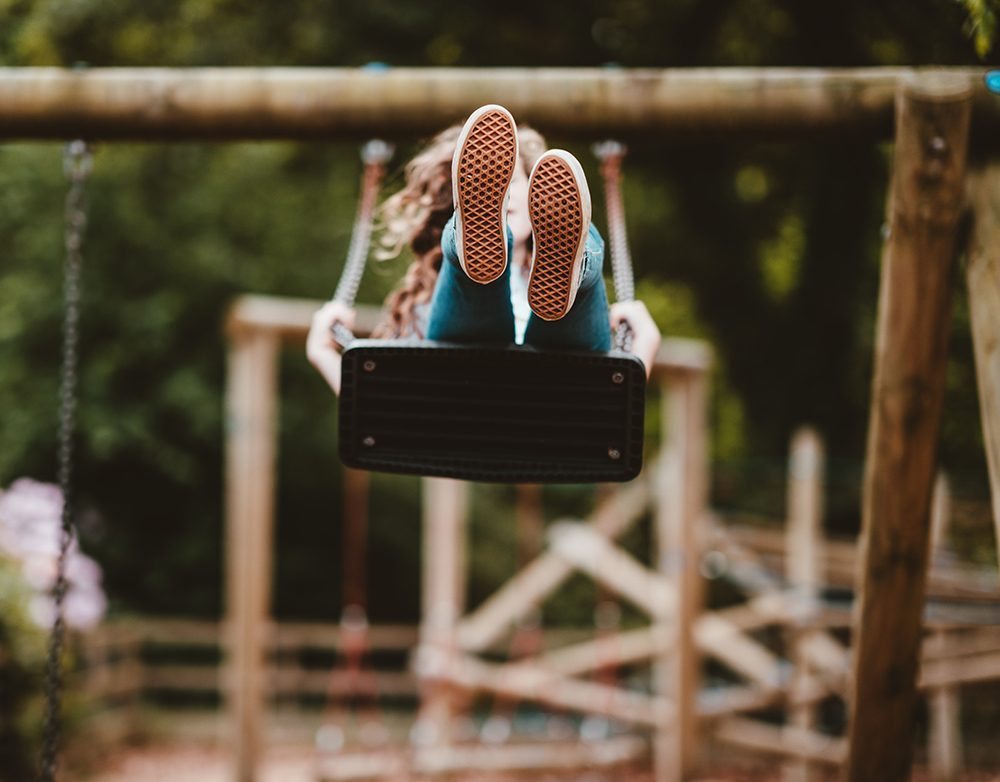 Child swinging on a swing, feet in the air