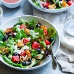 Salad bowl with spoon on white table cloth